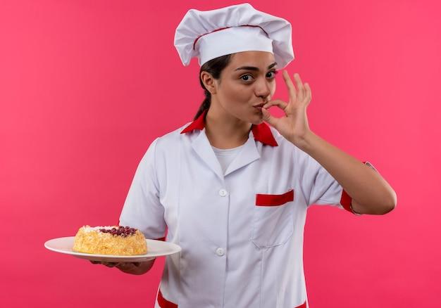 La giovane ragazza caucasica felice del cuoco in uniforme del cuoco unico tiene la torta sul piatto e gesti il segno delizioso della mano gustoso isolato sulla parete rosa con lo spazio della copia