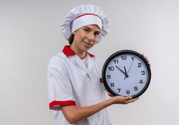 La giovane ragazza caucasica felice del cuoco in uniforme del cuoco unico tiene l'orologio su bianco con lo spazio della copia