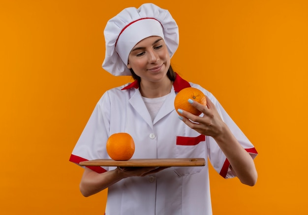 La giovane ragazza caucasica felice del cuoco in uniforme del cuoco unico tiene le arance sul tagliere e nella mano isolata sullo spazio arancione con lo spazio della copia