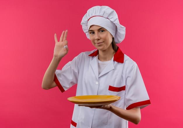 La giovane ragazza caucasica felice del cuoco in uniforme del cuoco unico tiene il segno giusto della mano di gesti e del piatto isolato sullo spazio rosa con lo spazio della copia