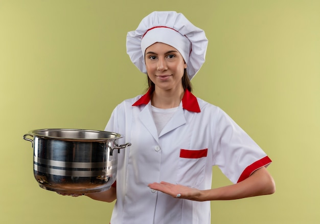 Young pleased caucasian cook girl in chef uniform holds and points at pot isolated on green background with copy space