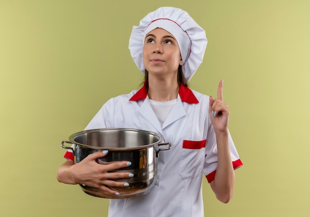 Young pleased caucasian cook girl in chef uniform holds pot and points up isolated on green background with copy space