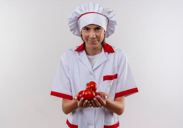 La giovane ragazza caucasica felice del cuoco in uniforme del cuoco unico tiene i pomodori sulle mani su bianco con lo spazio della copia