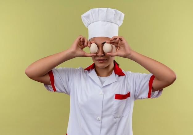 シェフの制服を着た若い喜んでいる白人料理人の女の子は、コピースペースで緑の壁に分離された卵で目を閉じます