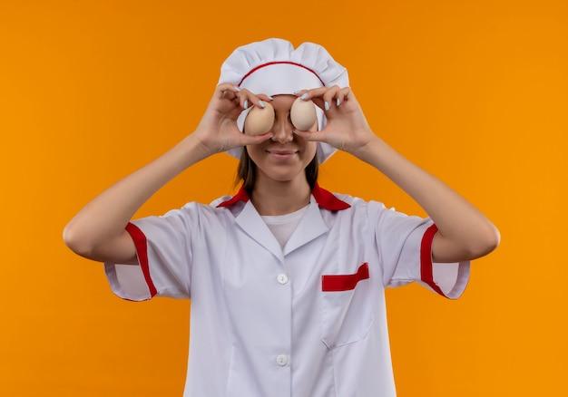 Молодая довольная кавказская девушка-повар в униформе шеф-повара закрывает глаза яйцами на апельсине с копией пространства