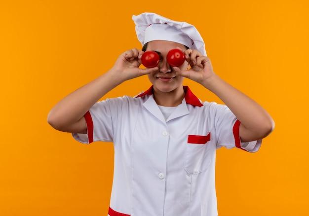 シェフの制服を着た若い喜んでいる白人料理人の女の子は、コピースペースでオレンジ色の壁に分離されたトマトで目を閉じます