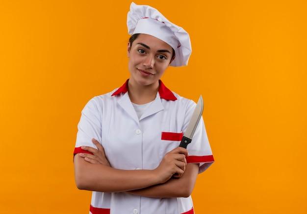 シェフの制服を着た若い喜んで白人料理人の女の子が腕を組んで、コピースペースでオレンジ色の壁に分離されたナイフを保持します。