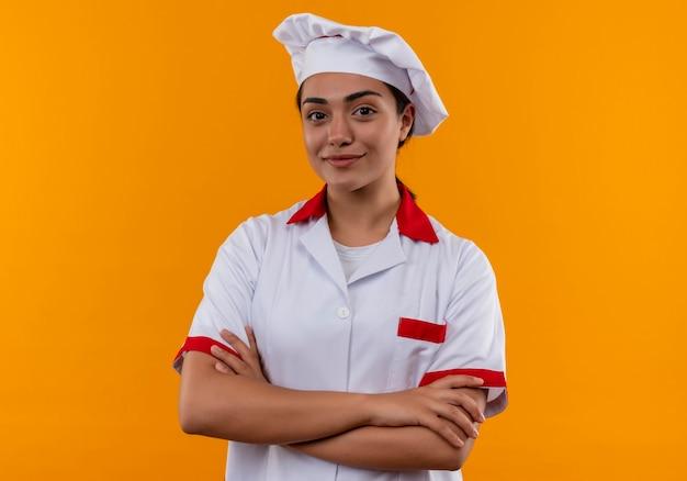 シェフの制服を着た若い喜んで白人料理人の女の子は、コピースペースでオレンジ色の壁に分離された腕を交差させます