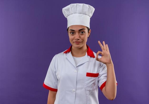 コピースペースで紫色の壁に分離されたシェフの制服のジェスチャーで若い満足している白人料理人の女の子