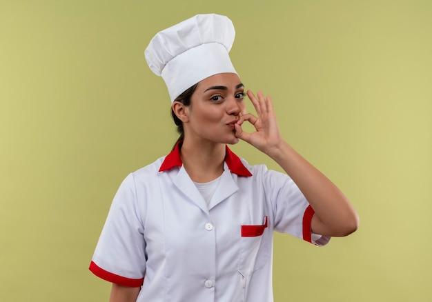 コピースペースと緑の壁に分離されたシェフの制服ジェスチャーおいしいおいしい手サインで若い喜んで白人料理人の女の子