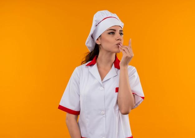 コピースペースでオレンジ色の壁に分離されたシェフの制服ジェスチャーおいしいおいしい手サインで若い喜んで白人料理人の女の子