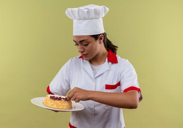 シェフの制服を着た若い喜んで白人料理人の女の子は、コピースペースで緑の壁に分離されたプレート上のケーキを保持し、見ています
