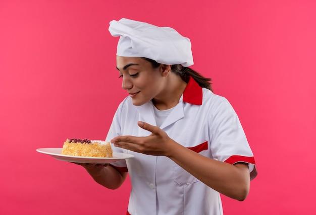 Молодая довольная кавказская девушка-повар в униформе шеф-повара держит и смотрит на торт на тарелке, изолированной на розовой стене с копией пространства