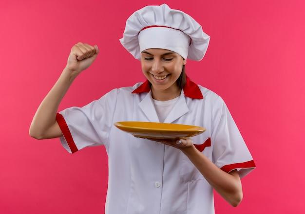 シェフの制服を着た若い喜んでいる白人料理人の女の子は、コピースペースでピンクの上げられた握りこぶしでプレートを保持し、見ています