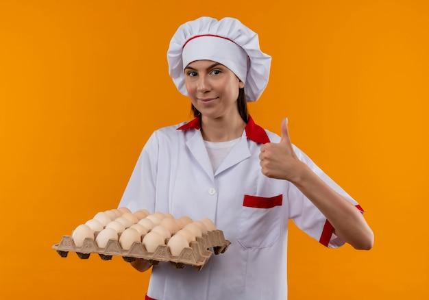 Молодая довольная кавказская девушка-повар в униформе шеф-повара держит партию яиц и большие пальцы руки вверх изолирована на оранжевом пространстве с копией пространства