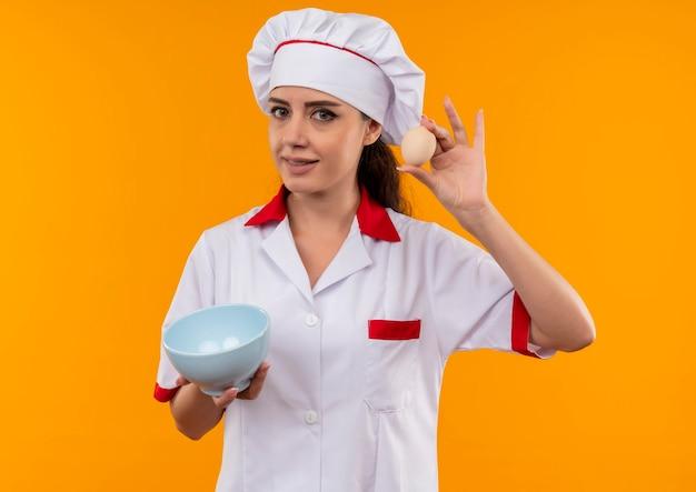 シェフの制服を着た若い喜んで白人料理人の女の子は、コピースペースでオレンジ色の壁に分離されたボウルと卵を保持します