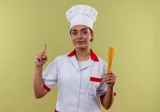 シェフの制服を着た若い喜んでいる白人料理人の女の子は、スパゲッティの束を保持し、コピースペースで緑の壁に隔離されたポイント