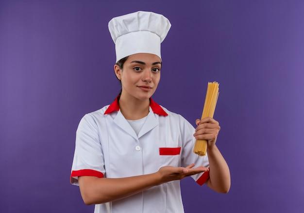 シェフの制服を着た若い喜んでいる白人料理人の女の子は、コピースペースで紫色の壁に隔離された手でスパゲッティとポイントの束を保持