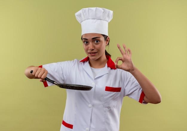 シェフの制服を着た若い喜んでいる白人の料理人の女の子は、フライパンを保持し、コピースペースで緑の壁に分離された手のサインをジェスチャーします