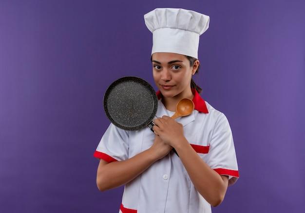 シェフの制服を着た若い喜んで白人料理人の女の子は、コピースペースで紫色の壁に分離されたフライパンと木のスプーンを保持します。
