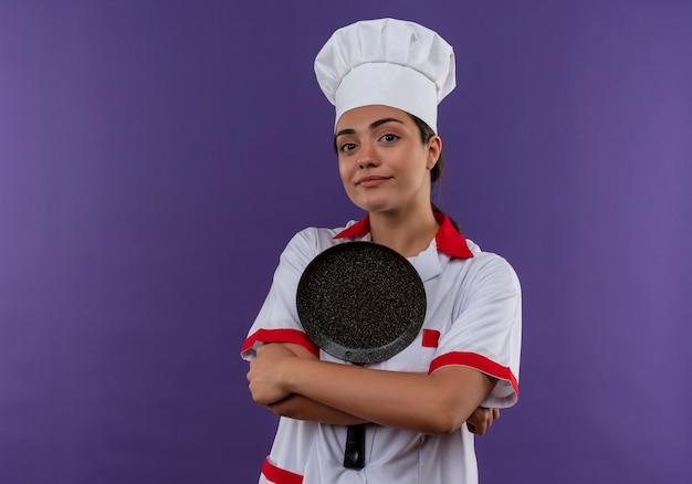 シェフの制服を着た若い喜んで白人料理人の女の子は、コピースペースで紫色の壁に隔離された腕でフライパンを保持します。