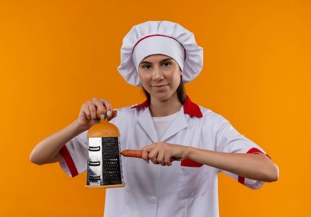 シェフの制服を着た若い喜んでいる白人料理人の女の子は、コピースペースでオレンジ色のおろし金とニンジンを保持します