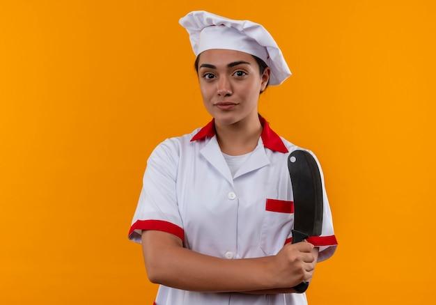 シェフの制服を着た若い喜んで白人料理人の女の子は、コピースペースでオレンジ色の壁に分離されたナイフを保持します