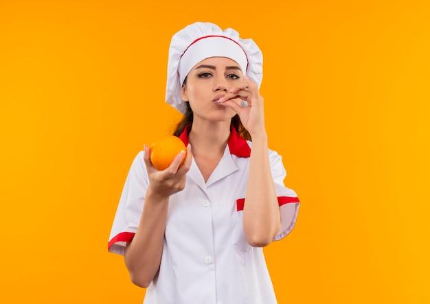 シェフの制服を着た若い喜んでいる白人料理人の女の子はオレンジ色を保持し、コピースペースでオレンジ色の壁に分離されたおいしいおいしいサインをジェスチャー