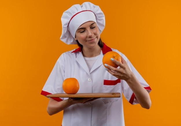 Молодая довольная кавказская девушка-повар в униформе шеф-повара держит апельсины на разделочной доске и в руке, изолированной на оранжевом пространстве с копией пространства