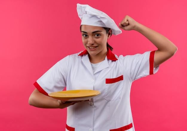 シェフの制服を着た若い幸せな白人料理人の女の子は、プレートを保持し、コピースペースでピンクの壁に分離された拳を上げます