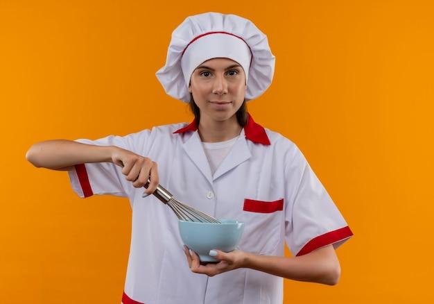 シェフの制服を着た若い喜んで白人料理人の女の子は、コピースペースでオレンジ色のスペースに分離された泡立て器とボウルを保持します