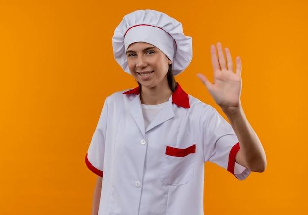 シェフの制服を着た若い喜んで白人料理人の女の子がコピースペースでオレンジ色の手を上げる