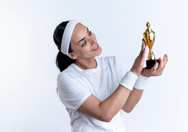 머리띠와 팔찌를 착용하는 젊은 만족 된 백인 스포티 한 여자가 보유하고 복사 공간이 흰색 공간에 고립 된 우승자 컵을 본다
