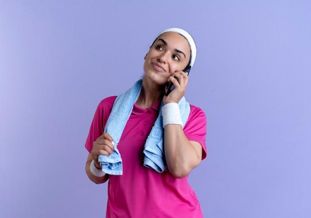 ヘッドバンドとリストバンドを身に着けている若い満足している白人のスポーティな女性は、コピースペースで紫色の電話で話している首の周りにタオルを保持します