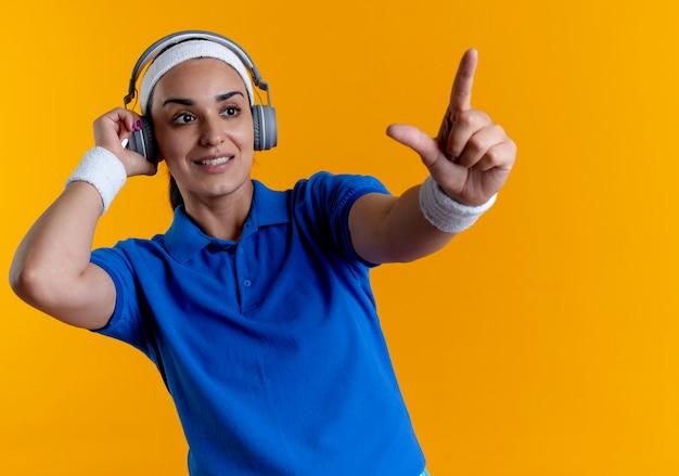 ヘッドフォンにヘッドバンドとリストバンドを身に着けている若い喜んでいる白人のスポーティな女性は、コピースペースとオレンジ色の背景で隔離の前方を指します