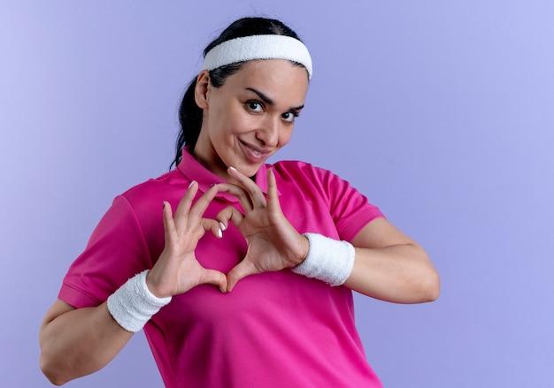 Giovane donna sportiva caucasica felice che indossa la fascia e braccialetti gesti il segno della mano del cuore isolato sullo spazio viola con lo spazio della copia