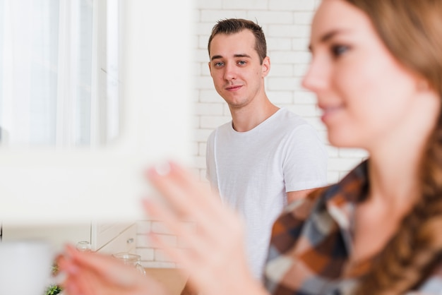 Young pleased couple in kitchen at home