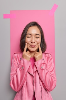Young pleased dark haired asian woman forces smile keeps index fingers near corners of lips closes eyes has happy dreamy expression wears fashionable pink jacket poses indoor