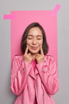 Молодая довольная темноволосая азиатская женщина заставляет улыбаться, держит указательные пальцы возле уголков губ, закрывает глаза, имеет счастливое мечтательное выражение, носит модную розовую куртку, позирует в помещении