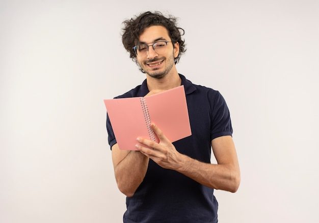 Young pleased man in black shirt with optical glasses holds and looks at notebook isolated on white wall