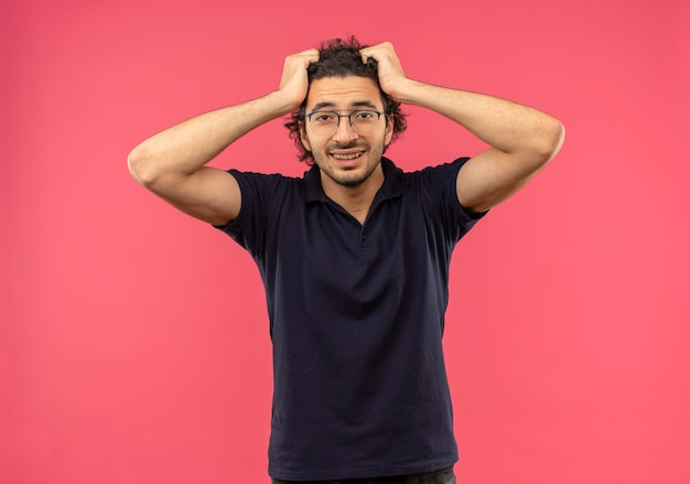 光学メガネと黒のシャツを着た若い喜んでいる男は髪を保持し、ピンクの壁に孤立して見える