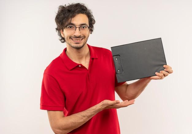 光学メガネと赤いシャツを着た若い喜んでいる男は、白い壁に分離されたクリップボードを保持し、ポイントします