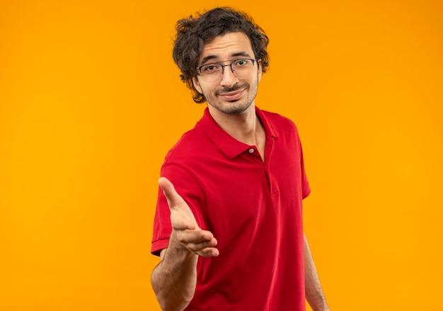 光学メガネと赤いシャツを着た若い喜んでいる男は、オレンジ色の壁に隔離された手を差し伸べる