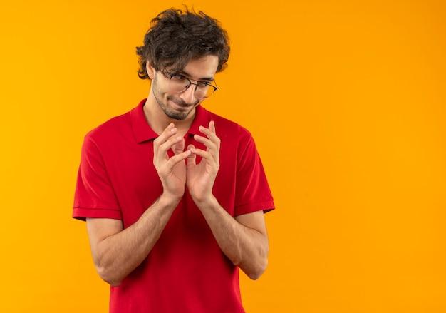 光学ガラスと赤いシャツを着た若い喜んでいる男は、手をつないで、オレンジ色の壁に隔離された側を見ます