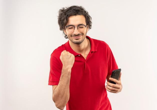 光学メガネと赤いシャツを着た若い喜んでいる男は電話を保持し、コピーspacで白い壁に拳を隔離し続けます