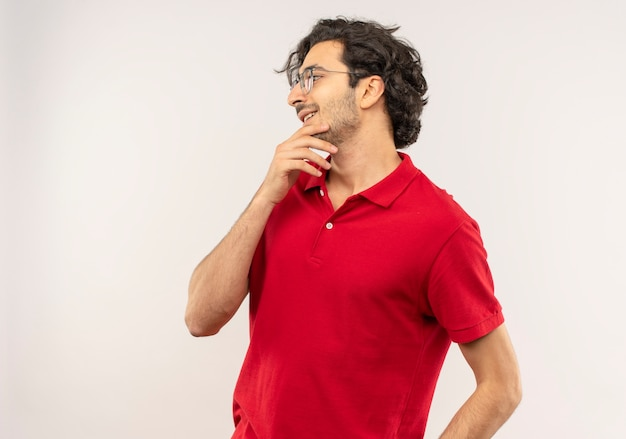 光学メガネと赤いシャツを着た若い喜んでいる男は、あごに手を置き、白い壁で隔離された側を見て