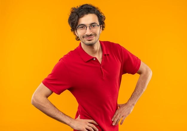 광학 안경 빨간 셔츠에 젊은 기쁘게 남자가 허리에 손을 놓고 오렌지 벽에 고립 된 모습