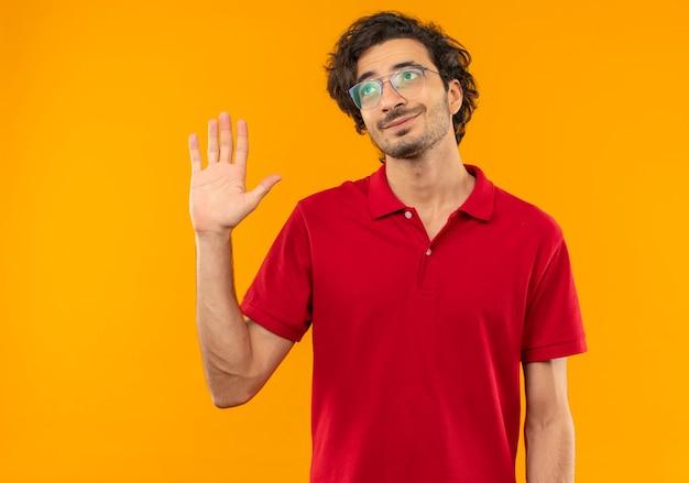 光学メガネと赤いシャツを着た若い喜んでいる男は手を上げて、オレンジ色の壁に孤立して見上げる