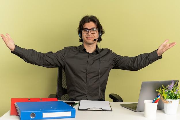 眼鏡をかけたヘッドフォンで若い満足しているサラリーマンの男は、ラップトップを使用して机に座って腕を開いたままにします