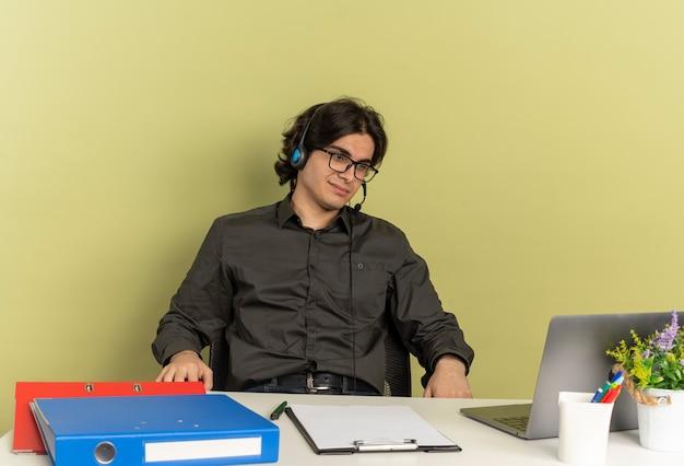 광학 안경에 헤드폰에 젊은 기쁘게 회사원 남자는 사무실 도구를 사용하고 복사 공간이 녹색 배경에 고립 된 노트북을보고 책상에 앉아